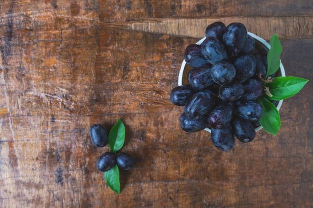 Uvas pretas em uma cesta em uma mesa de madeira