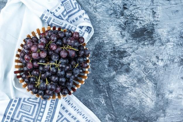 Uvas pretas em uma cesta plana sobre um fundo de gesso sujo e toalha de cozinha