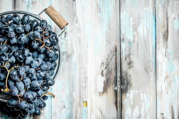 Uvas pretas em uma panela. sobre um fundo rústico.
