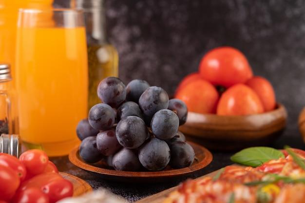 Uvas pretas em uma placa de madeira com tomates suco de laranja e pizza.