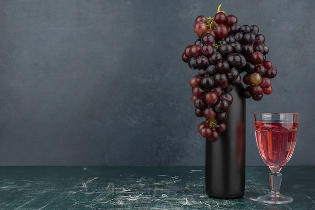 Uvas pretas em volta de uma garrafa e um copo de vinho na mesa de mármore