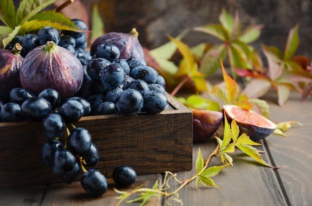 Uvas pretas frescas e figos na bandeja de madeira escura na mesa de madeira foco seletivo
