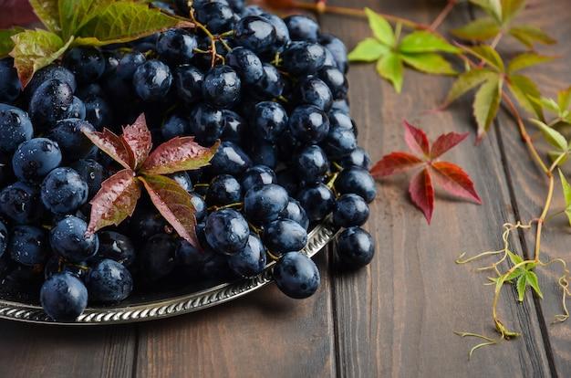 Uvas pretas frescas na placa de prata