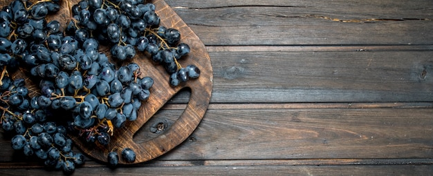 Uvas pretas maduras. sobre um fundo de madeira.