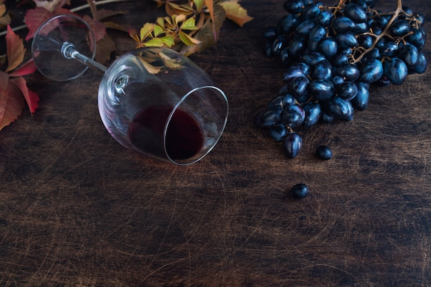 Uvas pretas orgânicas frescas e um copo com vinho tinto em fundo de madeira compensada rústica. espaço para texto.
