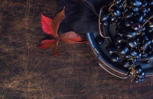 Uvas pretas orgânicas frescas em bandeja vintage em fundo de madeira compensada rústica. vista do topo. espaço para texto.