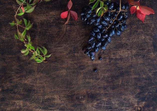 Uvas pretas orgânicas frescas em fundo de madeira compensada rústica. vista do topo. espaço para texto.
