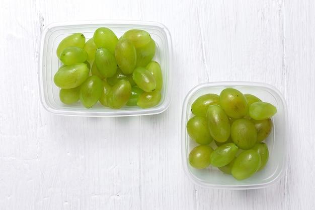 Uvas sazonais frescas em recipientes de plástico prontos para comer