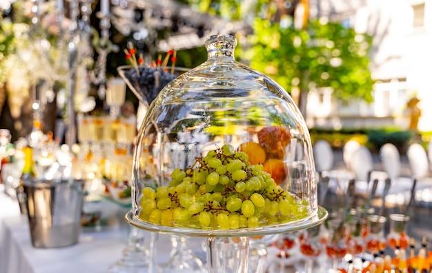 Uvas sob cobertura de cúpula de vidro transparente. sobremesa na mesa festiva. decoração de mesa de casamento. foco seletivo.