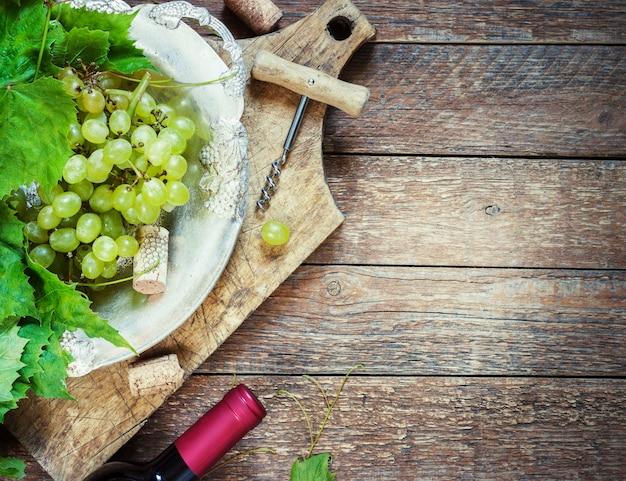 Uvas, uma garrafa de vinho, rolhas e saca-rolhas em uma mesa de madeira velha, estilo rústico