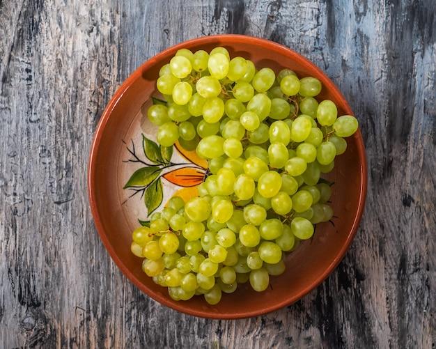 Uvas verdes alinhadas com uma lâmina em um prato de argila, close-up