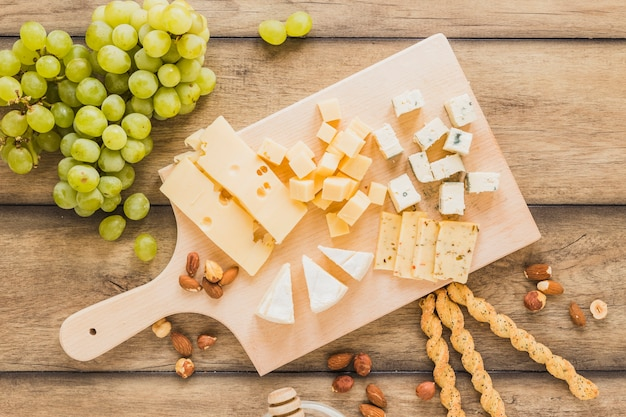 Uvas verdes, amêndoas, varas de pão e blocos de queijo na tábua de cortar sobre a mesa de madeira