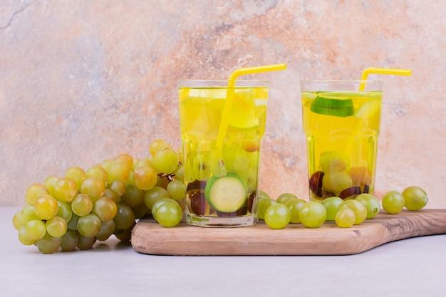 Uvas verdes com dois copos de suco em uma placa de madeira