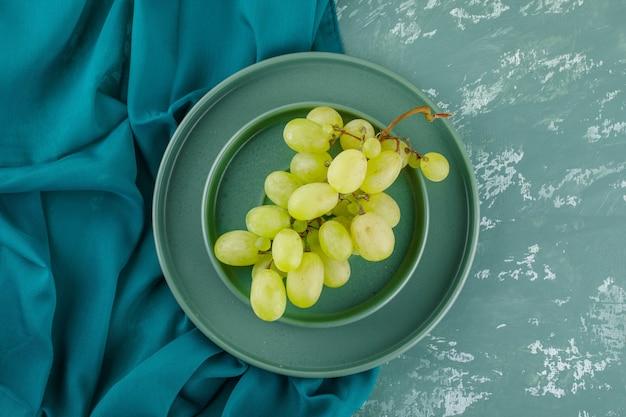 Uvas verdes com prato em pires em gesso e tecido,