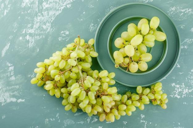 Uvas verdes com prato em pires sobre gesso,