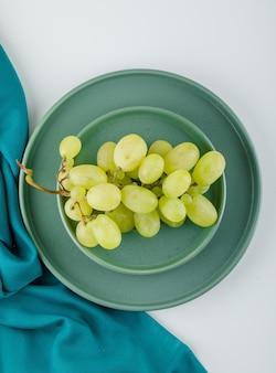 Uvas verdes com prato em um pires em branco e têxtil,