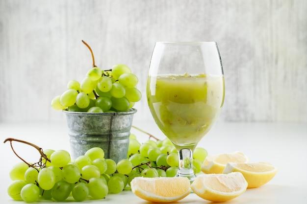Uvas verdes com rodelas de limão, coquetel de uva em um mini balde na superfície branca