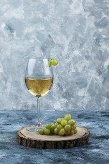 Uvas verdes com um copo de vinho em gesso sujo e fundo de pedaço de madeira, vista lateral.