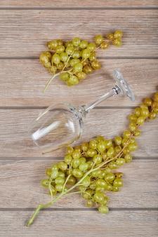 Uvas verdes com um copo de vinho vazio ao redor.