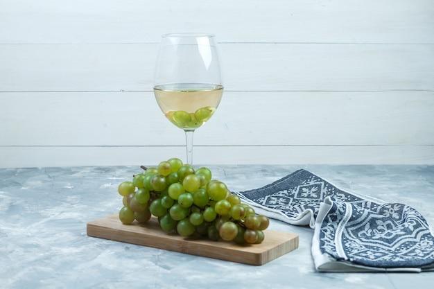 Uvas verdes de vista lateral com um copo de vinho, pedaço de madeira, toalha de cozinha em fundo cinza de madeira e sujo. horizontal
