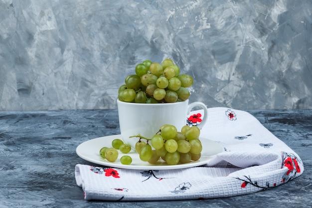 Uvas verdes de vista lateral em copo branco e placa em gesso sujo e fundo de toalha de cozinha. horizontal