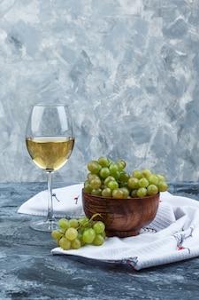 Uvas verdes de vista lateral em uma tigela com um copo de vinho no fundo de gesso e toalha de cozinha sujo. vertical