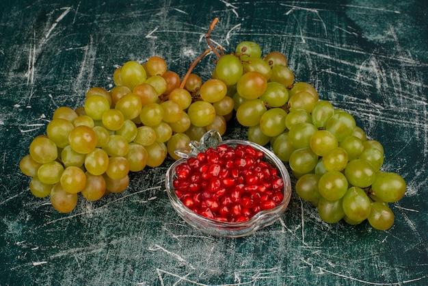 Uvas verdes e sementes de romã na superfície de mármore.