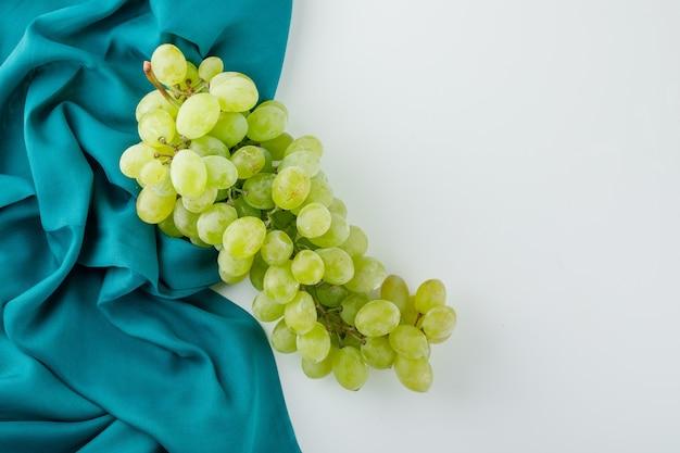 Uvas verdes em branco e têxtil,