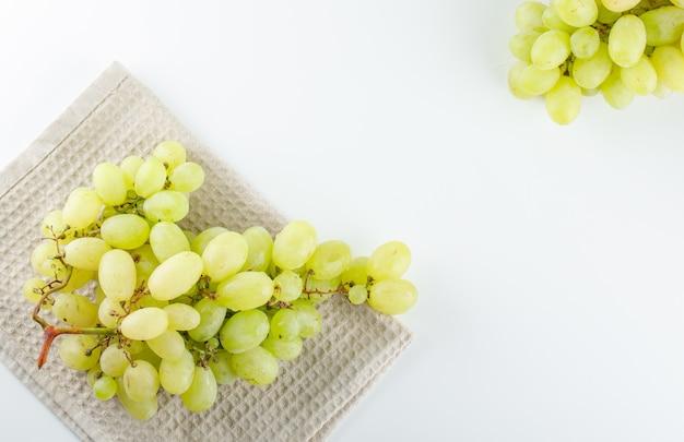 Uvas verdes em branco e toalha de cozinha,