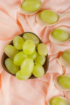 Uvas verdes em colheres de madeira e tigela em tecido rosa,