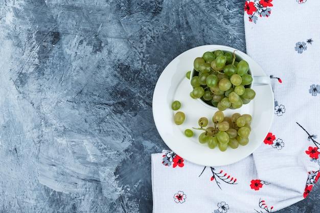Uvas verdes em copo branco e placa em gesso sujo e fundo de toalha de cozinha, plana leigos.