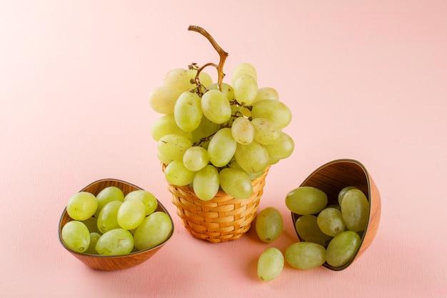 Uvas verdes em tigelas e cesta de vime em uma rosa. vista de alto ângulo.