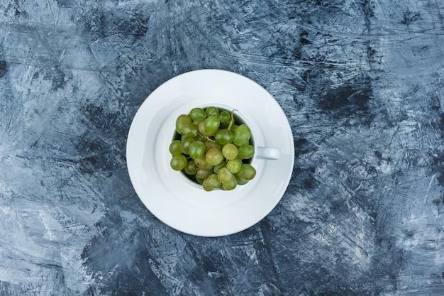 Uvas verdes em um copo branco com vista superior da placa em um fundo de gesso sujo