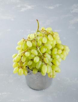 Uvas verdes em um mini balde em um gesso.