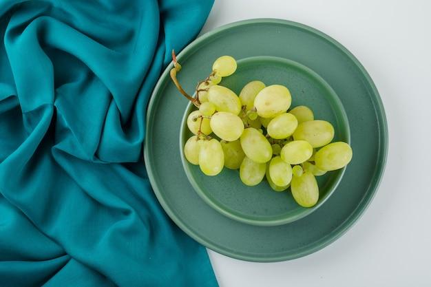 Uvas verdes em um pires com placa plana deitada em branco e têxtil
