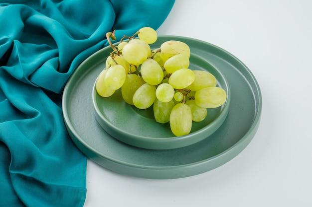 Uvas verdes em um pires com vista de alto ângulo da placa em branco e têxtil