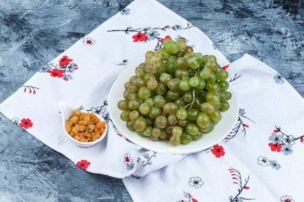 Uvas verdes em um prato branco com vista de alto ângulo de passas em gesso sujo e fundo de toalha de cozinha