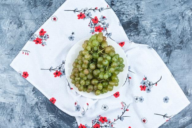 Uvas verdes em um prato branco sobre fundo de gesso e toalha de cozinha sujo, plano leigo.