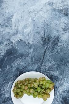 Uvas verdes em um prato branco sobre um fundo de gesso sujo. colocação plana.