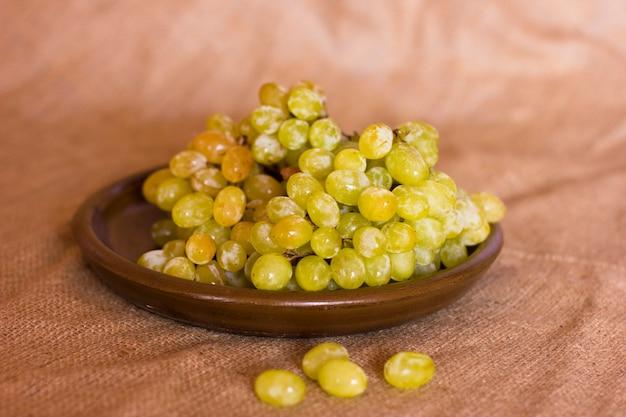 Uvas verdes em um prato de barro marrom