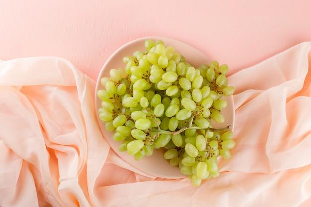 Uvas verdes em um prato plano deitado em rosa e tecido