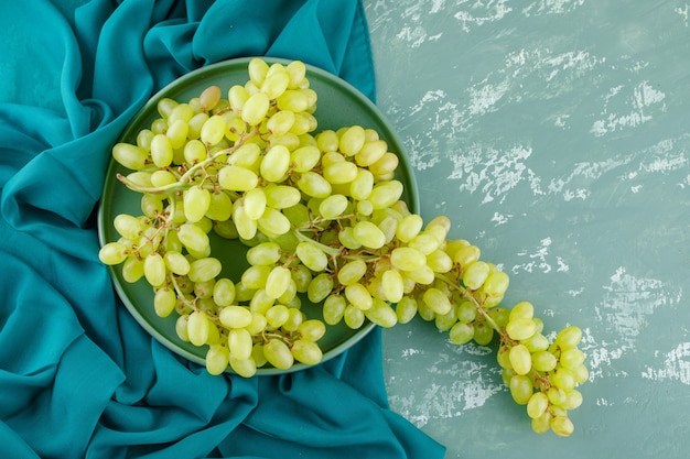 Uvas verdes em uma bandeja plana sobre gesso e tecido