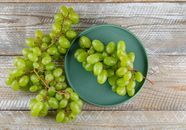 Uvas verdes em uma bandeja sobre um fundo de madeira. colocação plana.
