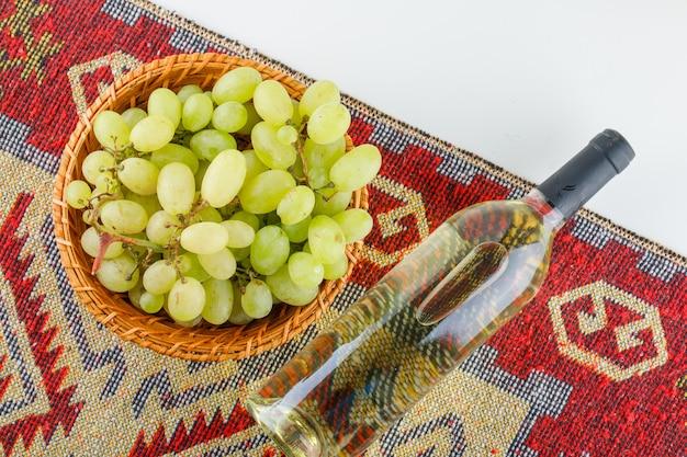 Uvas verdes em uma cesta com vinho plano deitado no tapete branco e kilim