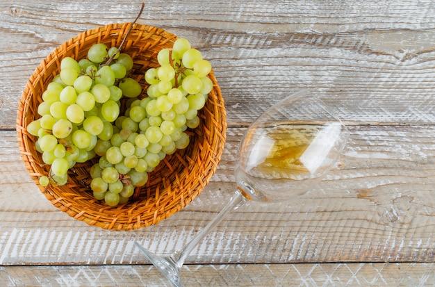 Uvas verdes em uma cesta de vime com bebida plana sobre um fundo de madeira