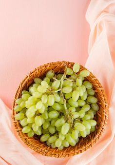 Uvas verdes em uma cesta de vime em rosa e têxteis.