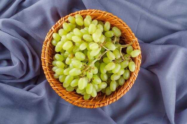 Uvas verdes em uma cesta de vime em tecido,
