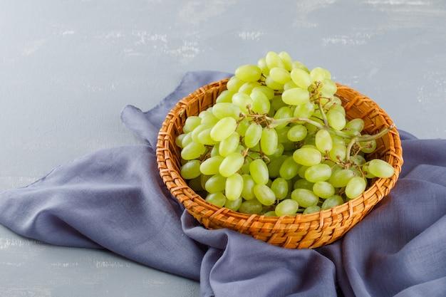 Uvas verdes em uma cesta de vime em têxteis e gesso, vista de alto ângulo.