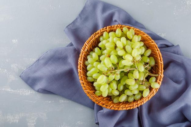 Uvas verdes em uma cesta de vime plana sobre tecido e gesso