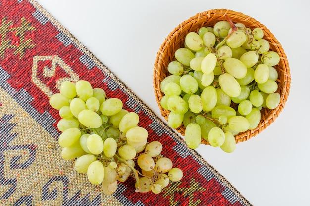 Uvas verdes em uma cesta no tapete branco e tradicional. colocação plana.